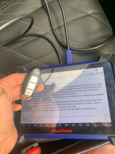 An automotive locksmith for Infiniti cars coding a new key fob on-site