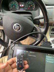 Automotive locksmith coding a new Jaguar key fob on-site with a special machine