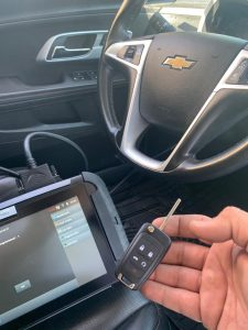 Auto locksmith coding a new key with special coding machine (Chevy)