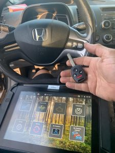 Automotive locksmith coding a new Honda key with a special machine on-site