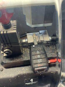 Automotive locksmith cutting a new Kia flip key