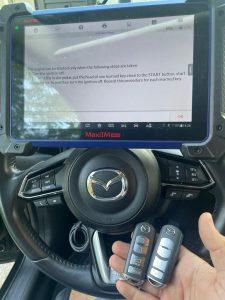 An automotive locksmith coding new Mazda key fobs