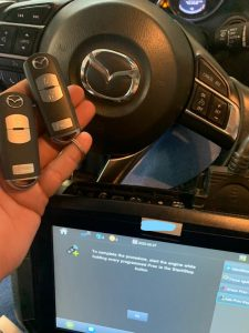Automotive locksmith coding a new Mazda key fobs on-site