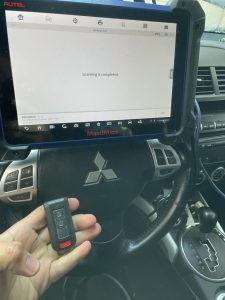 Automotive locksmith coding a new Mitsubishi key fob on-site