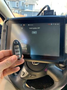 Automotive locksmith coding a new key fob on-site (Nissan)