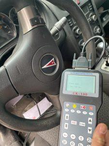 Automotive locksmith coding a new Pontiac key on-site