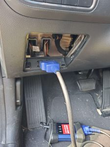 An automotive locksmith connecting coding machine to program a new BMW key replacement